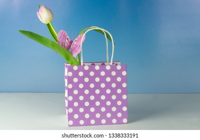 Purple gift bag with white dots and a butterfly and white tulip, blue background