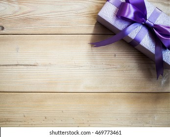 Purple gift box on wooden board. Copy space. Holidays concept