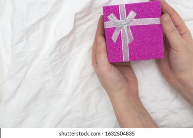 Purple Gift box. Present box for Holidays on white sheets of a bed Valentine's Day gift, International Women's Day gift over white bed linen background. Valentine's Gift or birthday closeup sparkle