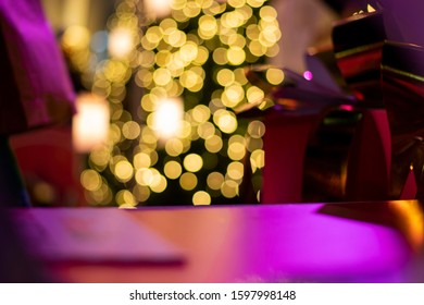 Purple gift box with yellow bokeh of lights on background.