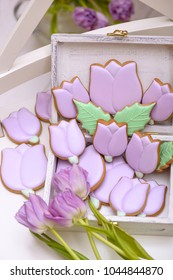 Purple gingerbread cookies in the shape of tulips with natural flowers. Holiday gift