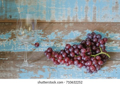 purple grapes and wine glass  on wood background.