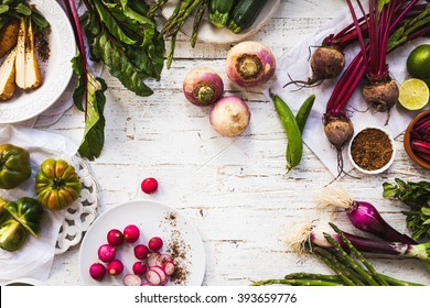 Purple and green veggies and roots composition on a rustic white wooden table. Beetroot, red onion, radish, asparagus, green tomatoes, parsnip, parsley ready to prepare salad. detox and diet food.