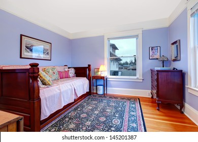 Purple guest bedroom with single wood day bed and blue rug.