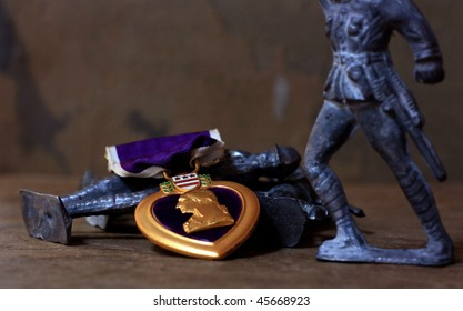 A Purple Heart Military Decoration Atop a Pile of Antique Toy Soldiers