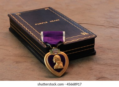A Purple Heart Military Decoration Draped in Front of its Box
