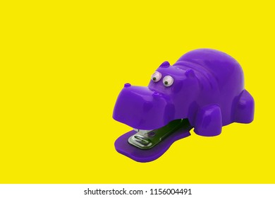 Purple Hippo stapeler in plastic on yellow background