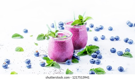 Purple homemade yogurt or smoothie with blueberries, chia seeds and mint leaves in glass jars on gray background, selective focus