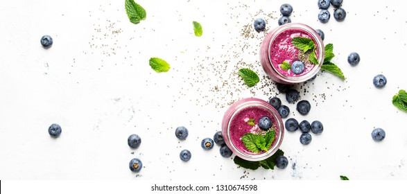 Purple homemade yogurt or smoothie with blueberries, chia seeds and mint leaves in glass jars on white background, flat lay, top view