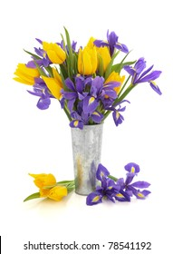 Purple iris and yellow tulip flower arrangement in an aluminum vase and loose isolated over white background.