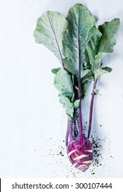 Purple kohlrabi with tops over light blue wooden background. Top view. With copyspace on left
