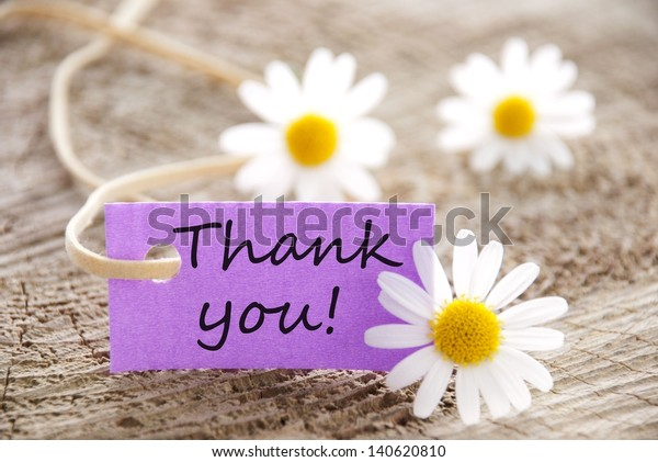 a purple label with Thank you on it and flowers in the background