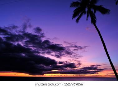 Purple, lavender and orange twilight after the sunset at Waimea Bay, North Shore, Oahu, Hawaii