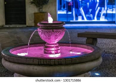 purple light in water falling in fountain