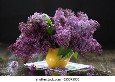 Purple lilac bouquet in a yellow vase