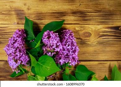Purple lilac on wooden background. Top view, copy space