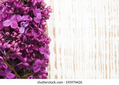 Purple Lilacs flowers on a wooden background