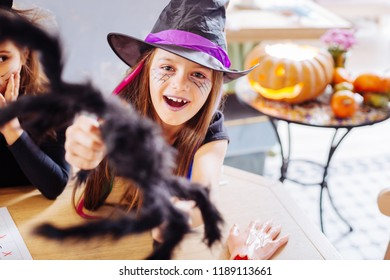 Purple lips. Beaming dark-haired girl with purple lips wearing wizard Halloween costume while attending party