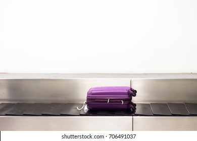 A purple luggage is laying down on the conveyor belt at the airport. Baggage claim. White wall background.