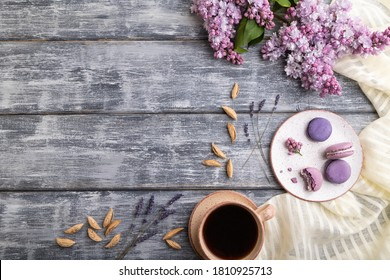Purple macarons or macaroons cakes with cup of coffee on a gray wooden background and white linen textile. Top view, flat lay, copy space.
