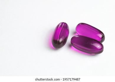 Purple medicine capsules on a white background