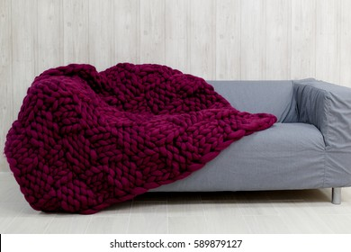 Purple merino wool blanket on grey sofa. Blanket of thick yarn. Chunky knit.