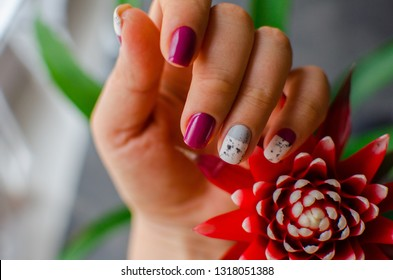 Purple nails on a pink background. Nails design  with beautiful red flower.