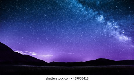 purple night sky stars with milky way over mountains. Italy, Castelluccio