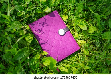 A purple notebook with a quilted cover is lying on the green grass, in the rays of the bright sun. Horizontal position, top view, close-up, space for text. Selectiv  focus