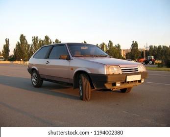 Purple old car hatchback half turn view. Photo exterior auto.