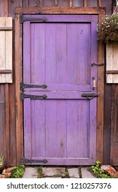A purple, old Dutch barn style garden shed door with vintage iron hardware is on a small wooden building.