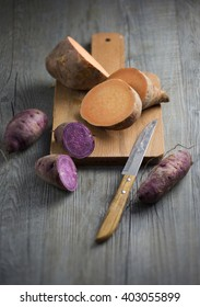 Purple and orange colour raw sweet potato on wooden chopping board on moody rustic wooden table top.