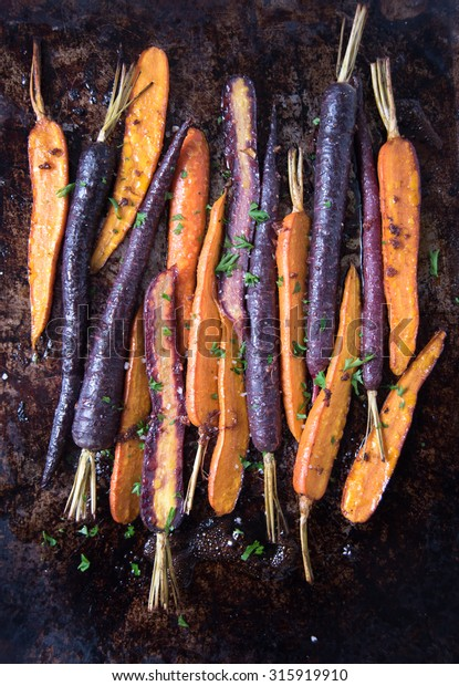 Purple and Orange Heirloom Carrots Roasted on Metal Sheet