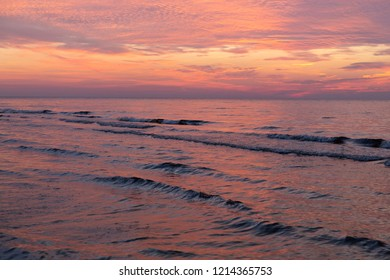 Purple orange sunset Baltic Sea and surf in autumn