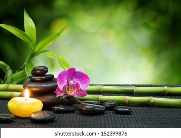 purple orchid, candle, with tower black stones , bamboo on black mat