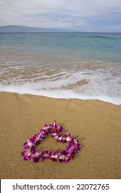 Purple orchid flower lei on a golden sandy tropical beach with island on distant horizon