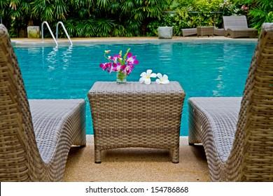 Violette Ochiden und Frangipani-Blumen mit Swimmingpool auf Rattan-Sessel