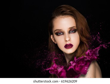 Purple paint splash over beauty makeup model girl with purple smokey eyes abstract on black background
