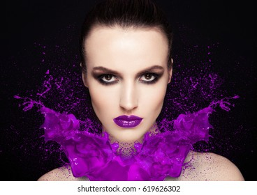Purple paint splash over beauty makeup model girl abstract on black background