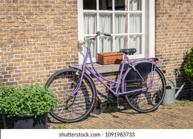 Purple painted ladies bike against an old brick wall in the Netherlands. It is a sunny day in the spring season.
