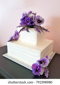 purple pansy bouquet on white tiered wedding cake