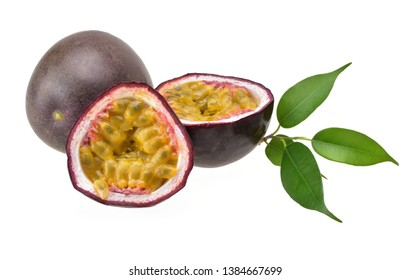 Purple passion fruit and two halves with ripe yellow flesh with green leaves on a neutral white background