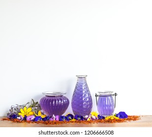 Purple  pea  essential  oil  in  glass  bottles   on  wooden  surface  with  white  background