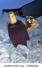 Purple perfume bottle lying on ice with a pair of sun glasses in the back
