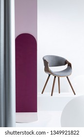 Purple pillar next to a gray chair in bright apartment interior with white walls. Real photo