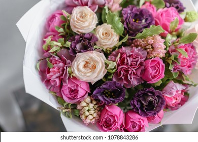 purple and pink bouquet of beautiful flowers on wooden table. Floristry concept. Spring colors. the work of the florist at a flower shop. Vertical photo