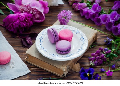 Purple and pink French macaroon cookies on a white plate on a book and a variety of pink and purple flowers on a wooden background