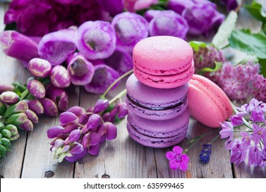 Purple and pink French macaroon cookies and a variety of flowers on a wooden background