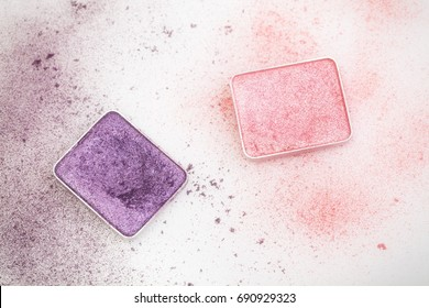 Purple and pink make-up palettes and crumbs on white