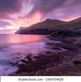 A purple and pink sunrise explosion along the Eidi coastline at Eidi in the Faroe Islands.